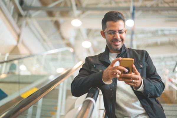 man browsing his phone on an escalator